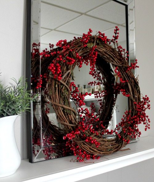 This DIY red berry wreath makes a beautiful festive holiday statement in your home and it only takes a few minutes and a few dollars to put together!