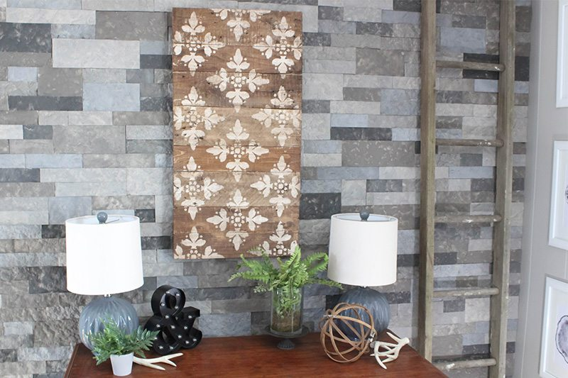 This wood wall art project is so easy to complete and will instantly bring farmhouse style to your home! The best part is that anyone can make wall art like this using a basic stencil and wood reclaimed from a shipping pallet!