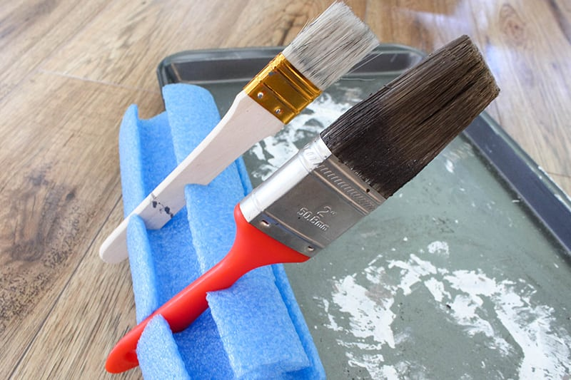 If you can never find a good place to put your brush down in between coats or when you're taking a break from painting, try making yourself a pool noodle paint brush stand!