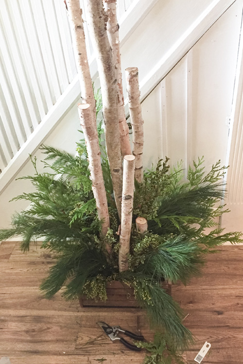 Create your own birch in a box Christmas planter for next to your front door with this easy tutorial! It's the perfect modern farmhouse style decor piece for your Christmas porch!