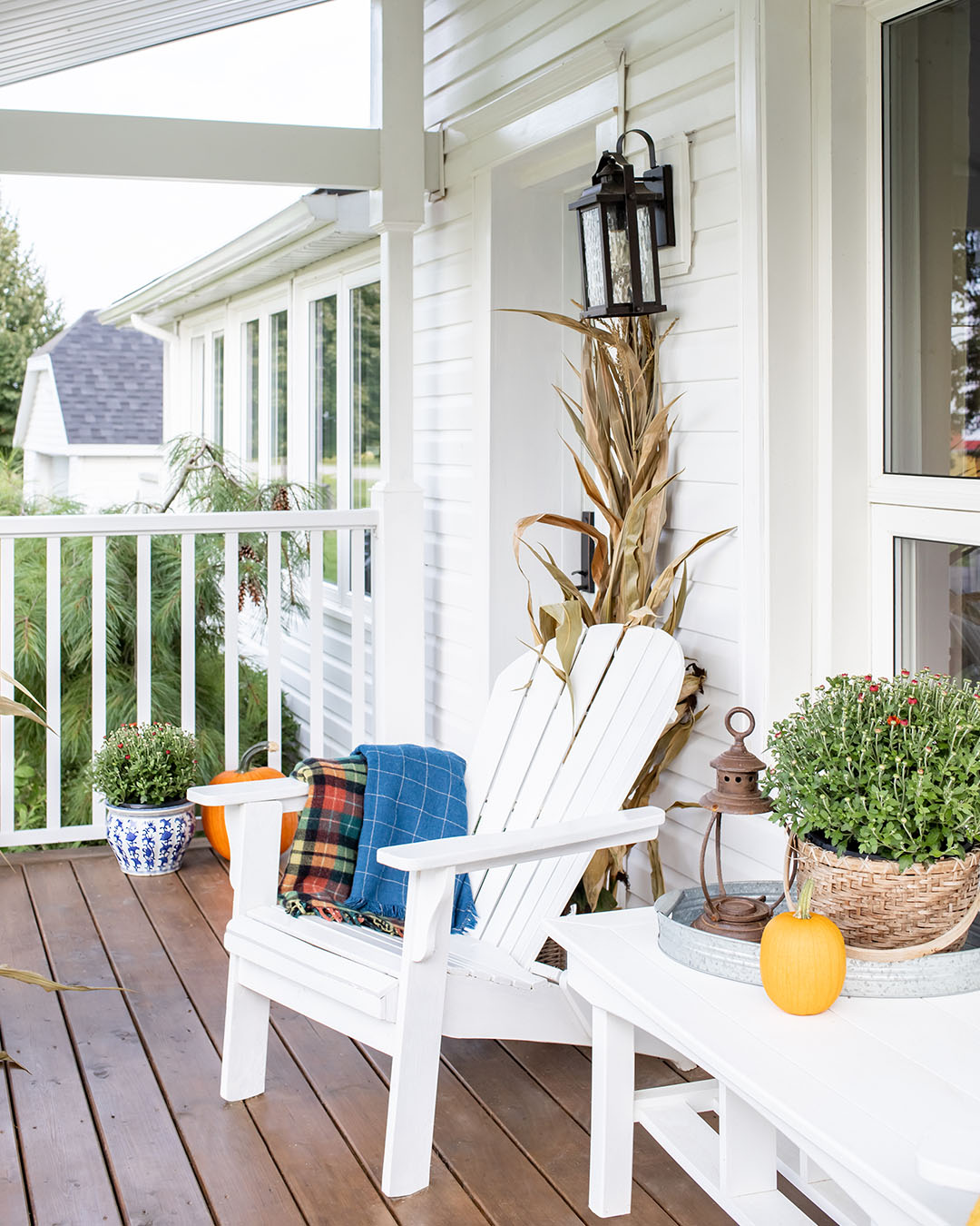 Fall weather is here! In today's post we'll share how we've decorated our classic farmhouse fall front porch this year with brightly coloured mums and cheerful orange pumpkins.
